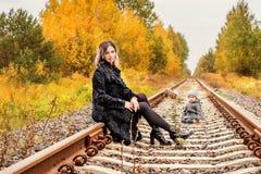 年轻美丽的妇女坐轨道在带着男孩和手提箱的森林在背景 库存图片