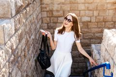 年轻美丽的妇女对一个石墙 免版税库存图片