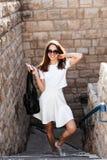 年轻美丽的妇女对一个石墙 免版税库存照片