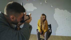 年轻美丽的妇女式样摆在摄影师的,当他射击与一台数字照相机在照片演播室户内时 图库摄影