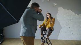 年轻美丽的妇女式样摆在摄影师的,当他射击与一台数字照相机在照片演播室户内时 库存照片