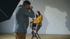 年轻美丽的妇女式样摆在摄影师的,当他射击与一台数字照相机在照片演播室户内时 免版税库存照片