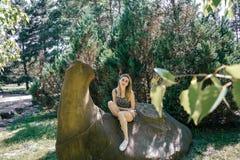 年轻美丽的妇女微笑的画象坐一个岩石在树木园 免版税图库摄影