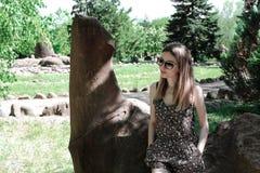 年轻美丽的妇女微笑的画象坐一块石头在树木园 免版税库存图片