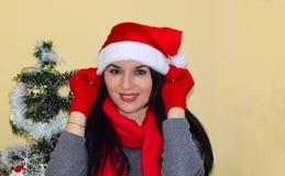 年轻美丽的妇女投入了圣诞老人` s盖帽 图库摄影