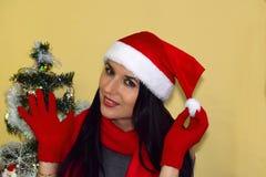 年轻美丽的妇女投入了圣诞老人` s盖帽 库存图片