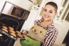 年轻美丽的妇女拉扯从烤箱的曲奇饼 免版税图库摄影