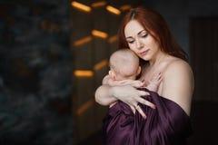 年轻美丽的妇女拥抱她新出生的婴孩 免版税库存图片