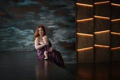 年轻美丽的妇女拥抱她新出生的婴孩 免版税图库摄影