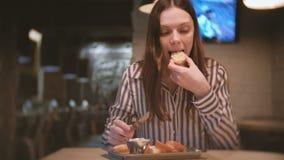 年轻美丽的妇女浅黑肤色的男人抹上在面包片的头脑在咖啡馆的与刀子 并且她吃三明治 股票视频