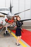 年轻美丽的妇女画象在企业喷气机的推进器的镀铬物纪念品的附近 免版税库存图片