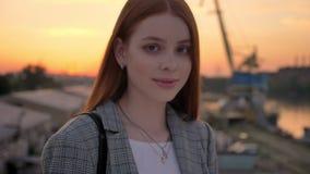年轻美丽的妇女画象有站立在桥梁和调查照相机,微笑,工厂的姜头发的和 影视素材