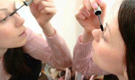 年轻美丽的妇女绘她的与染睫毛油的眼睛在镜子前面 侧视图 库存图片