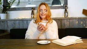 年轻美丽的妇女读在咖啡馆的一本书 她是微笑和享受咖啡芳香  影视素材