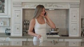 年轻美丽的妇女谈的手机、饮料咖啡或者茶在厨房里,愉快的微笑 库存图片