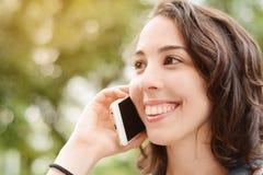 年轻美丽的妇女谈话与她的智能手机 免版税库存照片