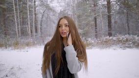 年轻美丽的妇女谈话在她的在多雪的背景的手机在冬天公园走户外 慢 股票录像
