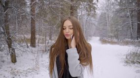 年轻美丽的妇女谈话在她的在多雪的背景的手机在冬天公园走户外 慢 股票视频