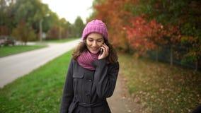 年轻美丽的妇女谈话在她的在黄色和红色叶子背景的手机,当走在秋天时 股票视频