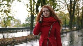 年轻美丽的妇女谈话在她的在黄色和红色叶子背景的手机,当走在秋天时 股票录像