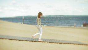年轻美丽的妇女走在耳机的海滩并且使用片剂 股票录像