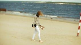 年轻美丽的妇女走在耳机的海滩并且使用片剂 股票视频