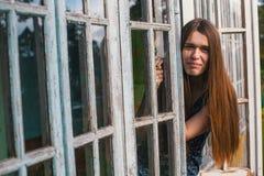 年轻美丽的妇女风长的头发坐窗口,夏天游廊 免版税库存图片