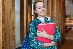 年轻美丽的学生女孩在她的手上站立与背包并且拿着文件夹 免版税图库摄影