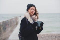 年轻美丽的少年女孩喝咖啡和在海滩 免版税库存图片