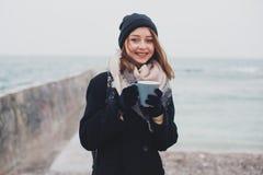 年轻美丽的少年女孩喝咖啡并且微笑 免版税库存照片
