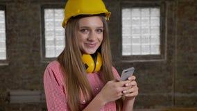 年轻美丽的微笑的女孩建造者使用她的智能手机,在照相机的watchig,通信概念 股票视频
