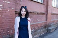 年轻美丽的微笑的女孩画象有棕色头发的在城市 免版税库存图片