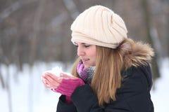 年轻美丽的微笑的妇女在手上的拿着雪在冬天ou中 库存照片