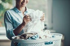 年轻美丽的微笑的妇女拿着干净的衣裳 免版税库存图片
