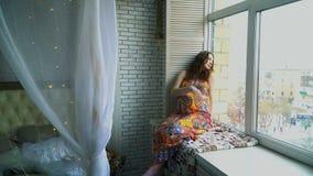 年轻美丽的怀孕的女孩在窗口附近坐 股票录像