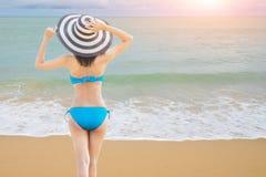 年轻美丽的性感的妇女佩带的比基尼泳装和放松在蓝色附近波浪的白色沙滩在热带海滩的 库存照片