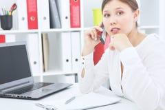 年轻美丽的惊奇的女商人谈话在坐在办公室的手机 免版税库存照片