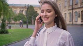 年轻美丽的愉快的女孩在电话谈话并且从大学去自白天在夏天,通信构想 影视素材