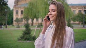 年轻美丽的愉快的女孩在电话谈话并且在公园进来自白天在夏天,通信构想 影视素材