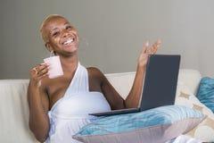 年轻美丽的愉快的黑人美国黑人的妇女微笑的研究便携式计算机在互联网onlin的沙发长沙发在家放松了 免版税图库摄影