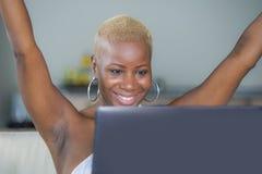 年轻美丽的愉快的黑人美国黑人的妇女微笑的研究便携式计算机在庆祝succe的沙发长沙发在家放松了 免版税库存图片