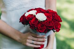 年轻美丽的新娘在她的手上拿着花束 免版税库存照片