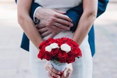年轻美丽的新娘在她的手上拿着花束 免版税库存图片