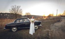 年轻美丽的新娘是其次近染黑减速火箭的汽车日落背景 婚姻与葡萄酒老减速火箭的汽车 妇女对负美丽 库存照片