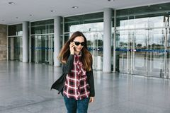 年轻美丽的旅游女孩在机场或在购物中心或驻地附近叫一辆出租汽车或谈话在细胞 免版税库存照片