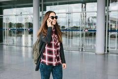 年轻美丽的旅游女孩在机场或在购物中心或驻地附近叫一辆出租汽车或谈话在细胞 库存图片