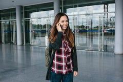 年轻美丽的旅游女孩在机场或在购物中心或驻地附近叫一辆出租汽车或谈话在细胞 免版税库存图片