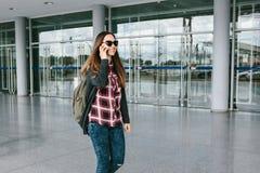 年轻美丽的旅游女孩在机场或在购物中心或驻地附近叫一辆出租汽车或谈话在细胞 库存照片