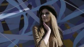 年轻美丽的时髦的女人画象有摆在蓝色graffity背景的黑帽会议的 r 式样佩带 股票视频