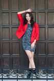 年轻美丽的时髦的妇女在一件红色外套,灰色穿戴了被编织的礼服,黑起动,以一个木门为背景 Str 免版税库存照片